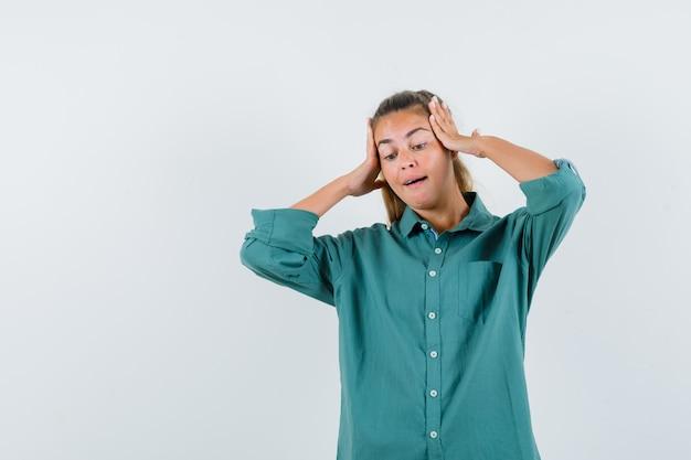 Giovane donna che mette le mani sulla testa in camicetta verde e che sembra carina