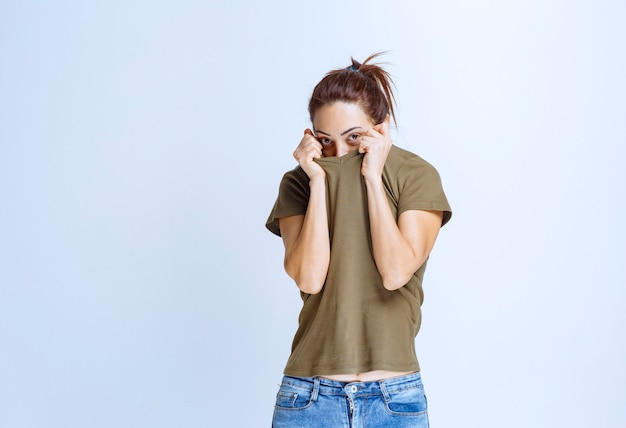 Young woman putting hands to her face and looks terrified and scared