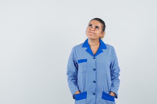 Молодая женщина кладет руки в карман, думая о чем-то в синей пижамной рубашке в клетку и задумчиво, вид спереди.