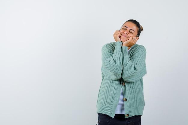頬に手を置き、白いシャツとミントグリーンのカーディガンで目を閉じて幸せそうに見える若い女性