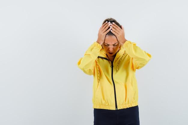 노란색 폭격기 재킷과 검은 색 바지에 머리에 손을 넣고 지쳐 보이는 젊은 여자