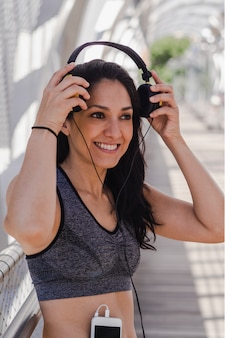 Young woman putting on headphones