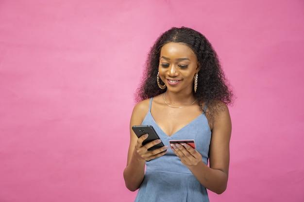 Молодая женщина кладет информацию о своей кредитной карте в свой мобильный телефон