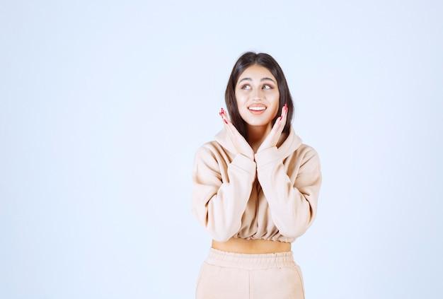 Giovane donna che si mette la mano al viso e ascolta con gioia