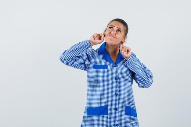 파란색 깅엄 파자마 셔츠에 귀 뒤에 검지 손가락을 넣고 잠겨있는, 전면보기를 찾고 젊은 여자.