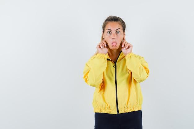 黄色のボンバージャケットと黒のズボンで舌を突き出し、かわいく見える間、耳に人差し指を置く若い女性