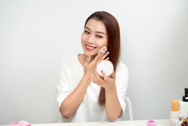 Молодая женщина наносит пудру для макияжа с косметической подушкой на кожу лица