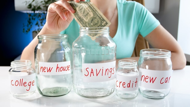 Young woman putting money in glass jar with her money savings. concept of financial investment, economy growth and bank savings.