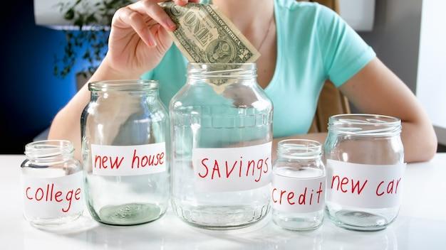 젊은 여자는 그녀의 돈 저축으로 유리 항아리에 돈을 걸고. 금융 투자, 경제 성장 및 은행 저축의 개념.