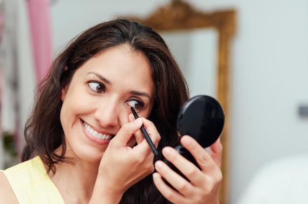 彼女のアイライン鉛筆で鏡の前で化粧をしている若い女性