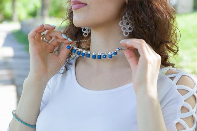 Молодая женщина надевает ожерелье в парке