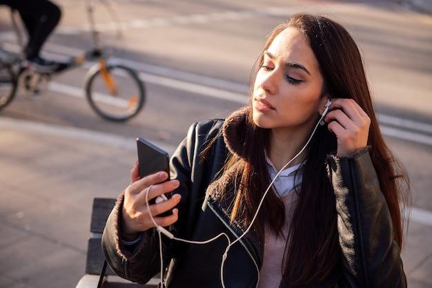 Молодая женщина надевает наушники своего телефона