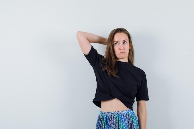 黒のtシャツと青いスカートで目をそらし、物思いにふけるように見ながら頭の後ろに片方の腕を置く若い女性