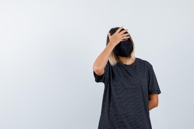 片方の手を額に、もう片方の手を腰の後ろに置き、黒いドレス、黒いマスクを上向きに見て、急いでいる若い女性、正面図。