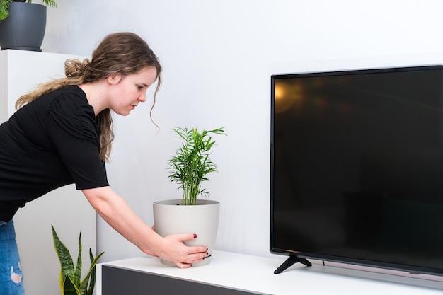 Молодая женщина сажает растения в свой новый дом