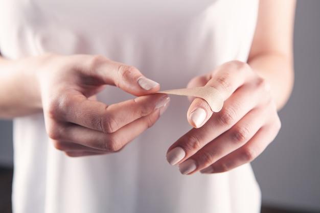Молодая женщина кладет гипс на палец