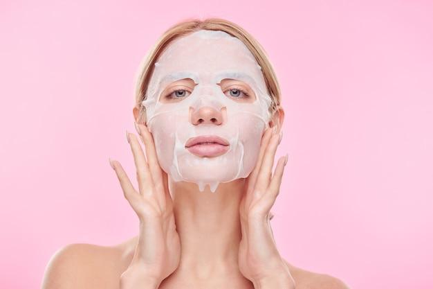 격리 된 피부를 돌보는 동안 그녀의 얼굴에 상쾌한 섬유 마스크를 넣어 젊은 여자