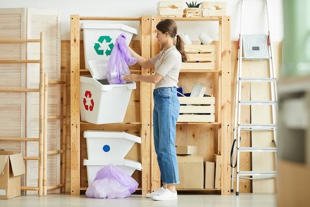 ゴミの入ったパッケージをプラスチックの容器に入れてゴミを分別する若い女性