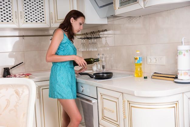 キッチンでお気に入りのレシピを調理しながらフライパンにワインを置く若い女性。
