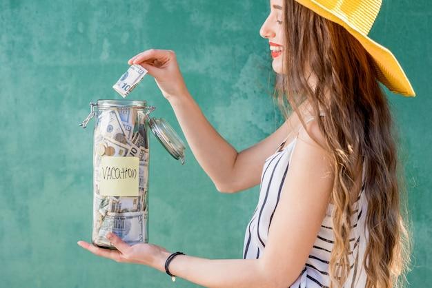 緑の背景の上に立っている夏休みのための貯蓄で瓶にお金を入れている若い女性