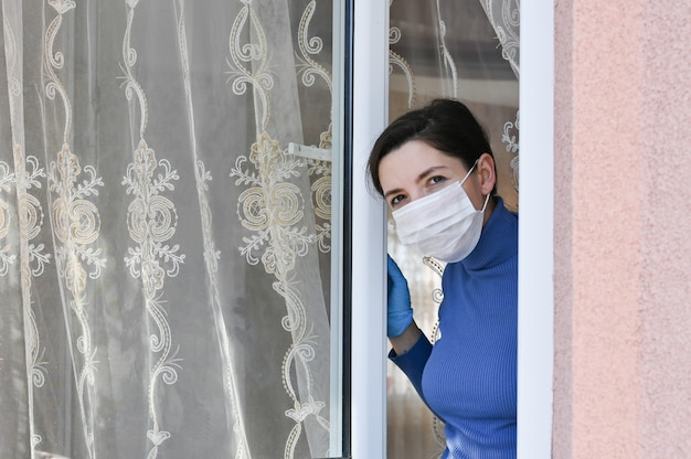 A young woman in quarantine with a mask looks out the window at home