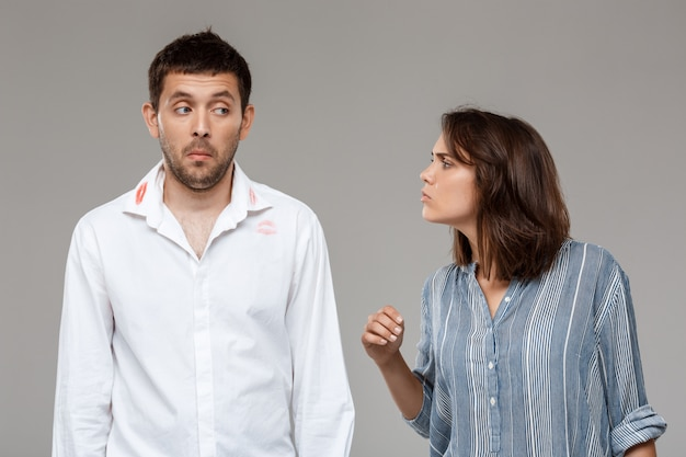 Young woman quarreling, angering with drunk husband over grey wall
