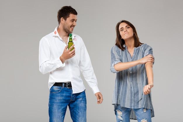 けんかばかりしている、灰色の壁に酔って夫と怒っている若い女性