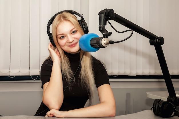 ヘッドフォンとマイクを備えたラジオスタジオの若い女性ラジオホストとライブトーク。駅でライブショーをホストするクリップボードを持つかわいい女性。リスナーのためのコンセプトラジオとインターネット放送