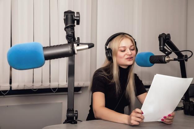 ヘッドフォンとマイクを備えたスタジオの若い女性ラジオホストとライブニュースを話します。駅でライブショーをホストするクリップボードを持つかわいい女性。リスナーのためのコンセプトラジオとインターネット放送