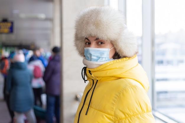 Giovane donna alla stazione ferroviaria in una maschera protettiva sul viso nel passeggero di abiti invernali