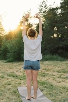 젊은 여성은 여름에 야외에서 휴식을 취하고 있는 초원의 햇살 가득한 곳에서 손을 들어 올립니다