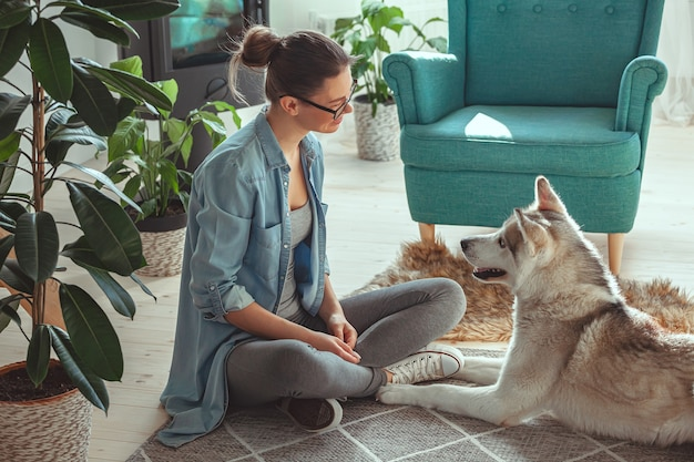 Молодая женщина воспитывает и играет со своей домашней собакой сибирский h