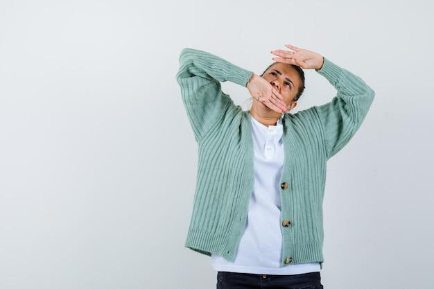 Giovane donna che alza le braccia e guarda sopra in camicia bianca e cardigan verde menta e sembra concentrata