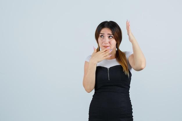 Giovane donna che alza la mano sopra la testa mentre tiene la mano sul mento