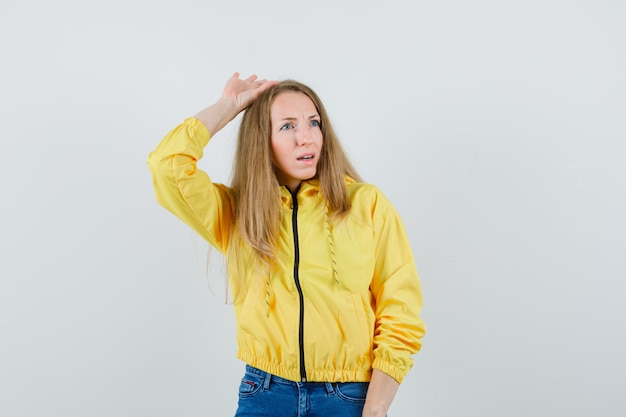 Young woman raising hand above head in yellow bomber jacket and blue jean and looking charming. front view.