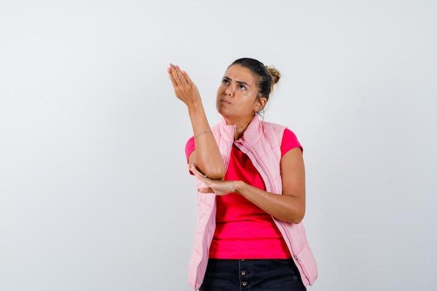 Giovane donna che alza la mano sopra, tenendo una mano sul gomito in maglietta e giacca rosa e sembra concentrata