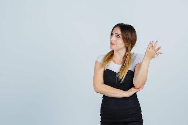 Giovane donna che alza la mano in un gesto perplesso