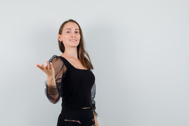 Молодая женщина поднимает руку с открытой ладонью в черной блузке и выглядит высокомерно
