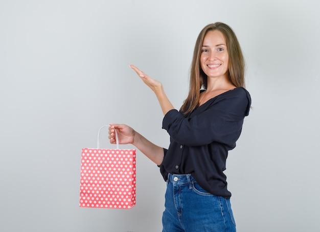 Giovane donna alzando la mano con il sacchetto di carta in camicia nera, pantaloncini di jeans