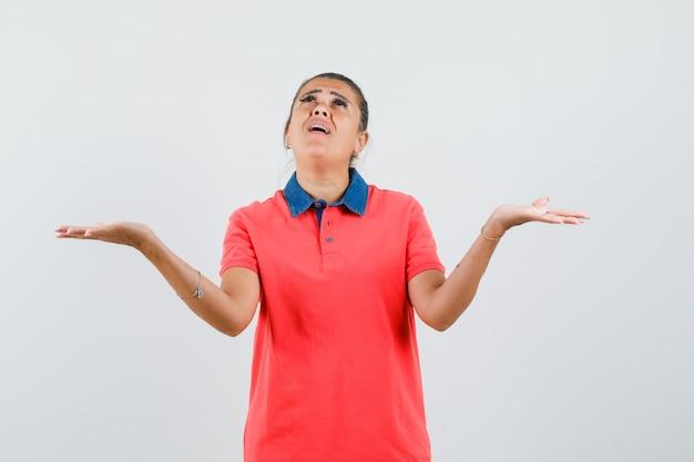 赤いtシャツで重いものを持ってイライラしているように手を上げている若い女性。正面図。
