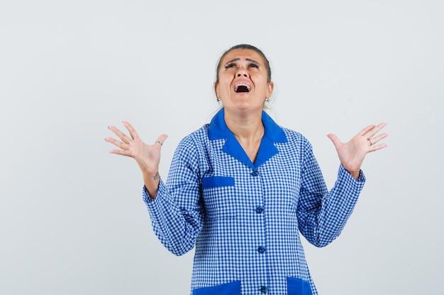 뭔가를 받고 파란색 깅엄 파자마 셔츠를 외치고 놀란 찾고 손을 올리는 젊은 여자. 전면보기.