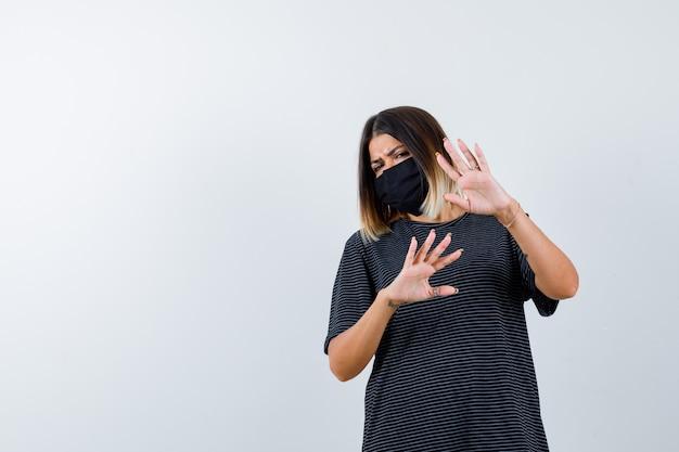 Giovane donna che alza le mani per fermarsi in abito nero, maschera nera e sembra spaventata, vista frontale.