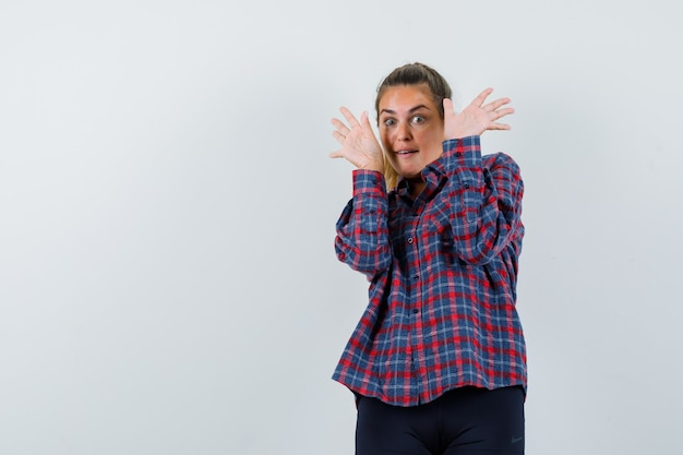 Young woman raising hands as to stop in checked shirt and looking surprised