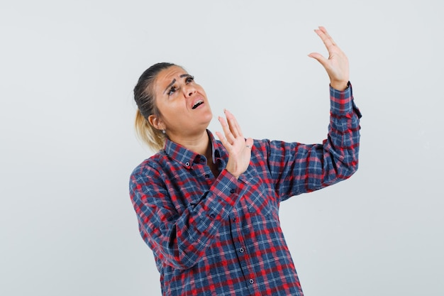 Young woman raising hands as trying to stop something in checked shirt and looking scared , front view.