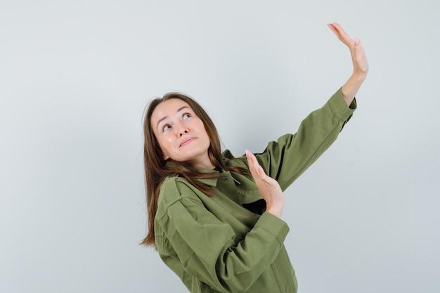 Giovane donna che alza le mani per difendersi in giacca verde e guardando concentrato, vista frontale.