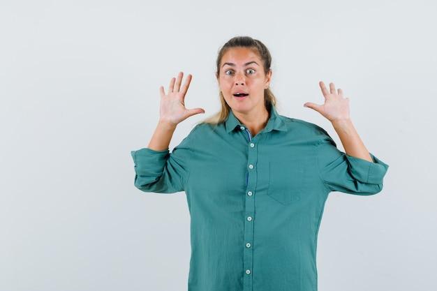 Молодая женщина поднимает руки для защиты в синей рубашке и выглядит встревоженной
