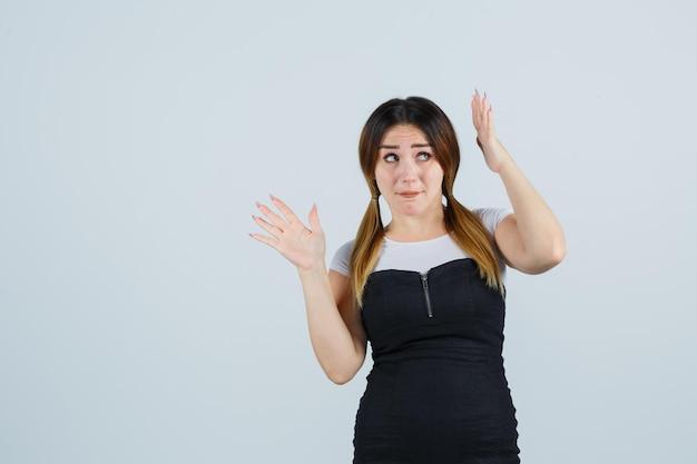 Giovane donna che alza le mani sopra la testa