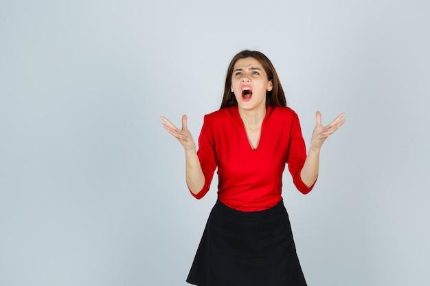 Молодая женщина сердито поднимает руки в красной блузке, черной юбке и выглядит сердитой