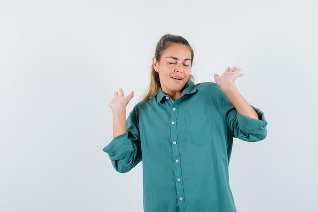 항복에 손을 올리는 젊은 여자가 녹색 블라우스에 포즈를 취하고 낙관적 인 찾고