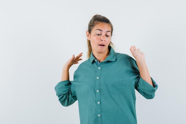 Молодая женщина поднимает руки в позе капитуляции в зеленой блузке и выглядит испуганной